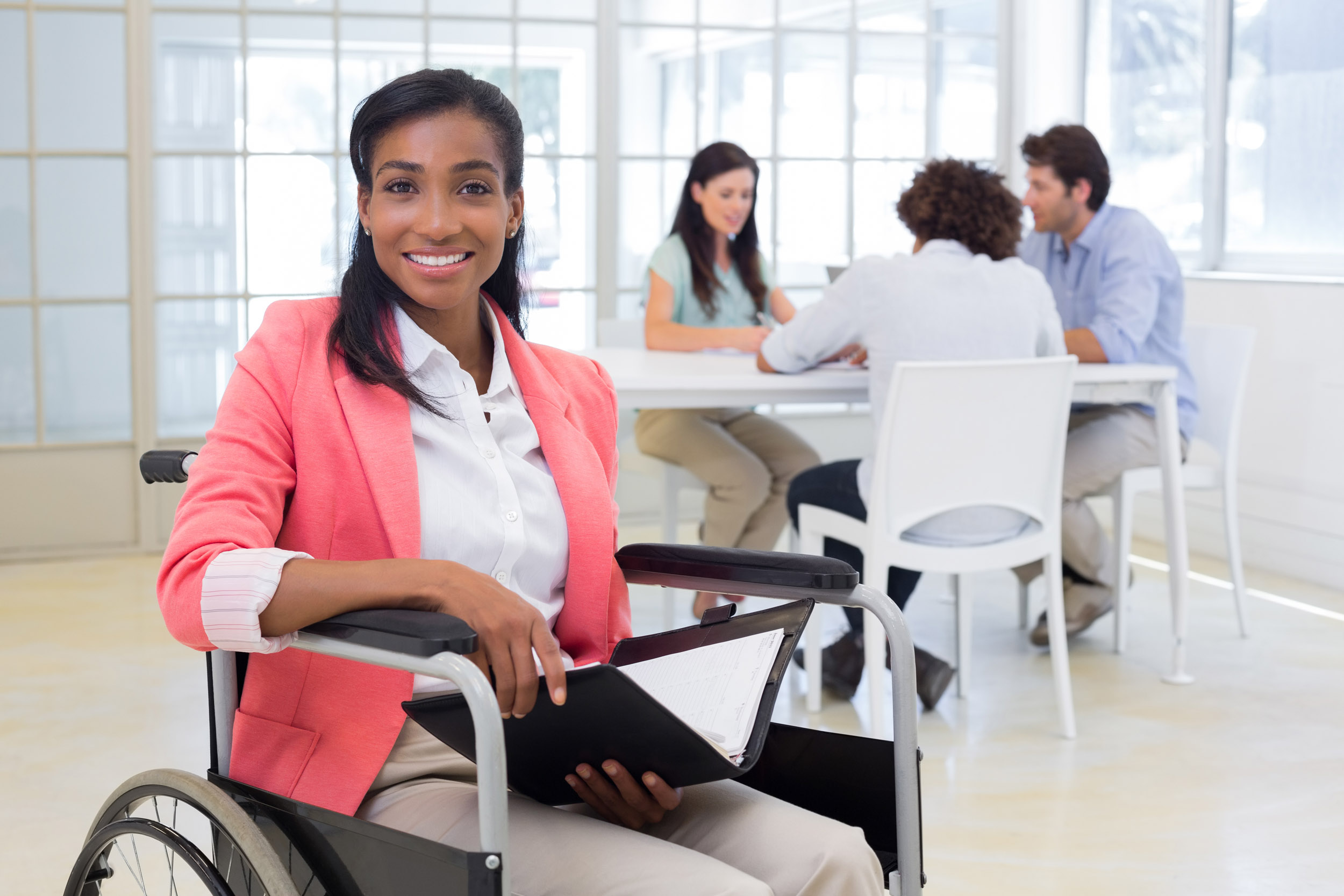Businesswoman in wheelchair holding folder and smiling at camera in the office