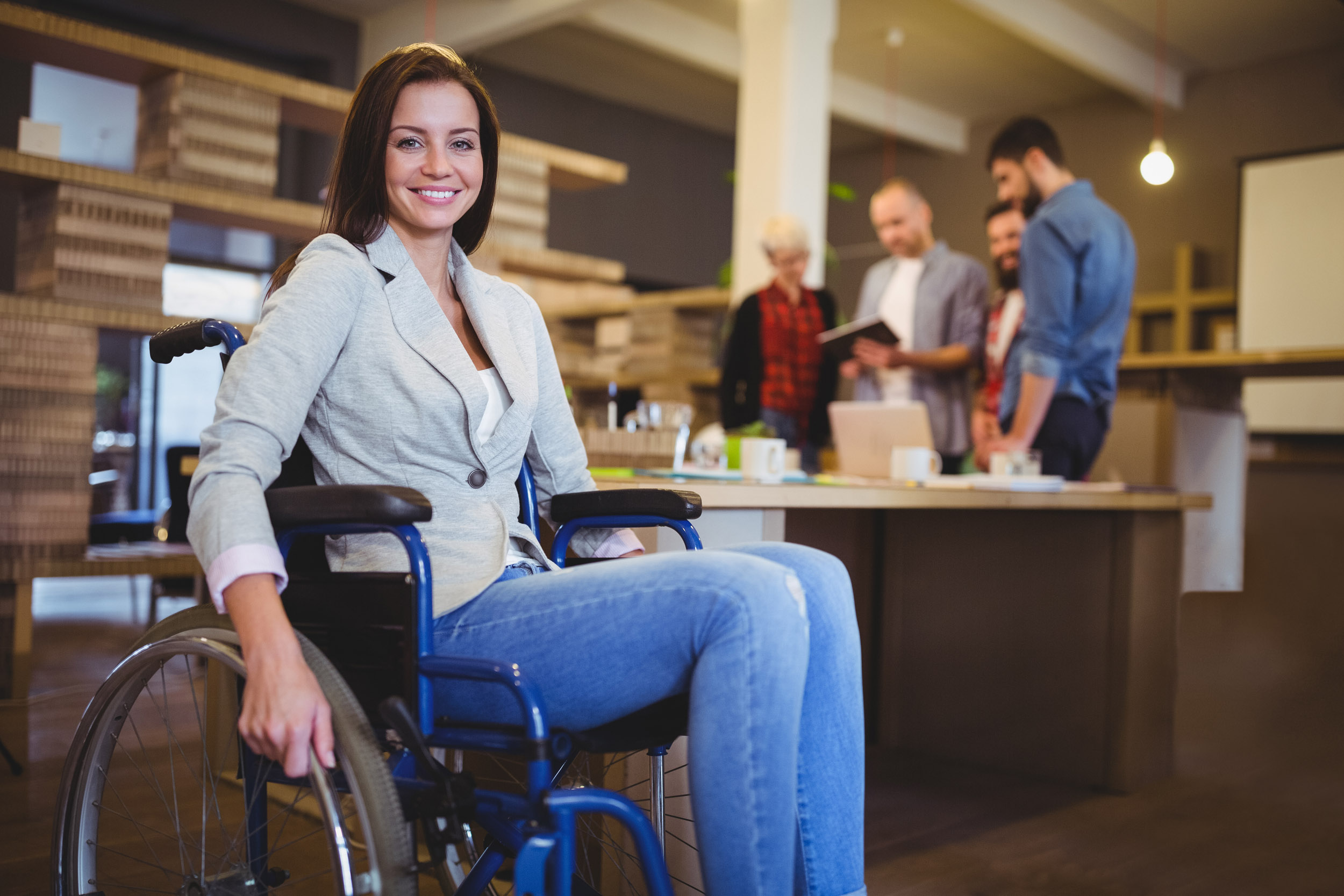 Portrait of confident disabled businesswoman by desk in creative office