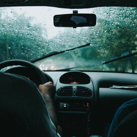 Backseat view of windshield wipers and rain