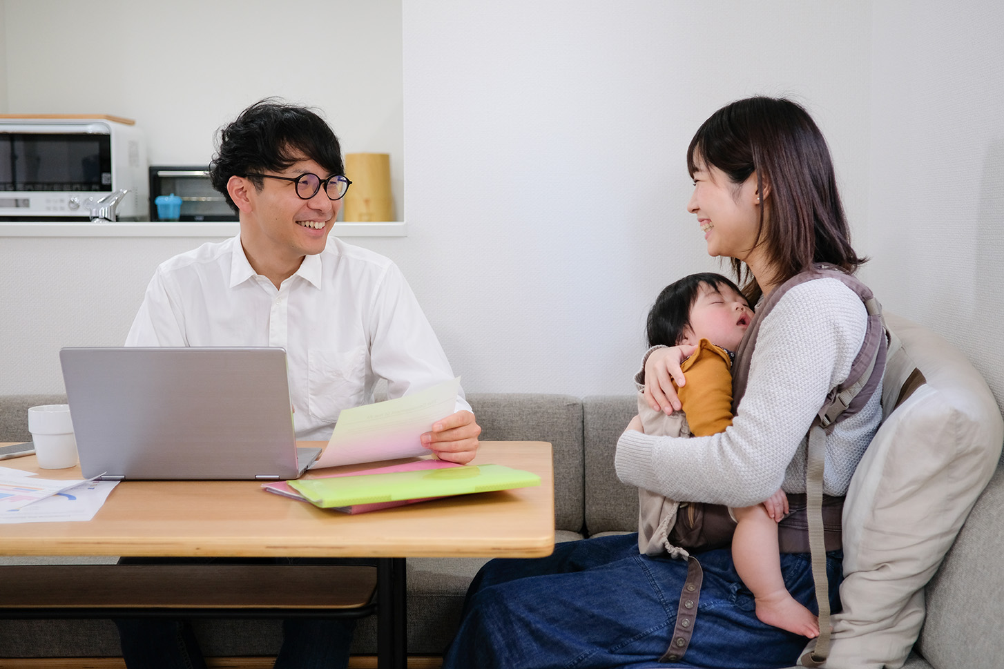 Husband working at home with wife and baby