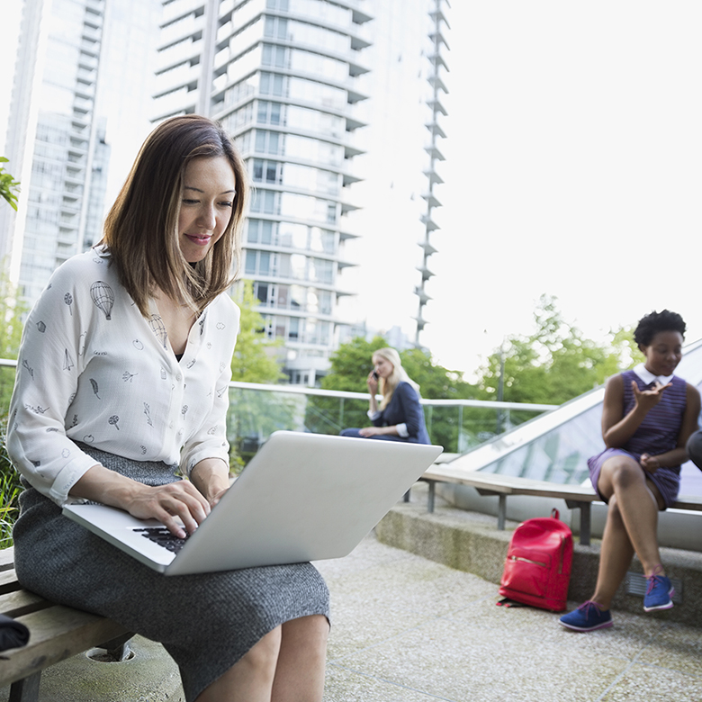 Businesswoman using laptop on bench in city