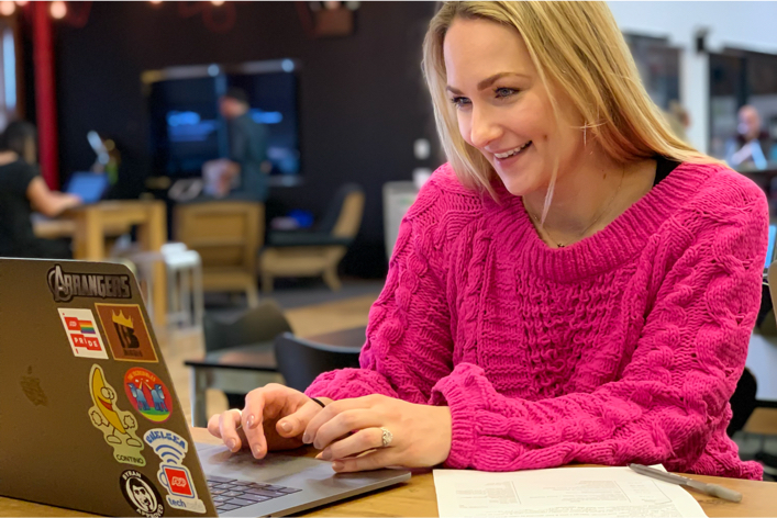Woman in hot pink sweater working on laptop