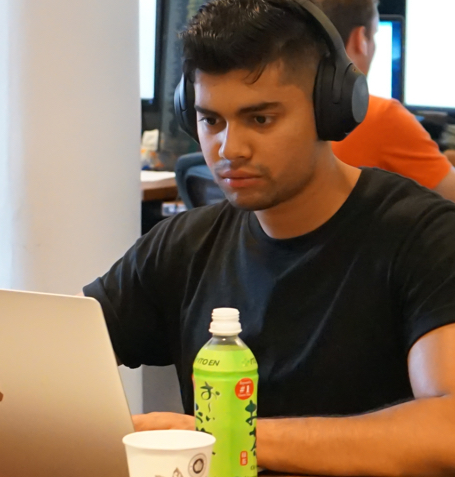 Man wearing headphones while working on a laptop