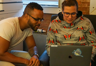Two employees look at a laptop screen