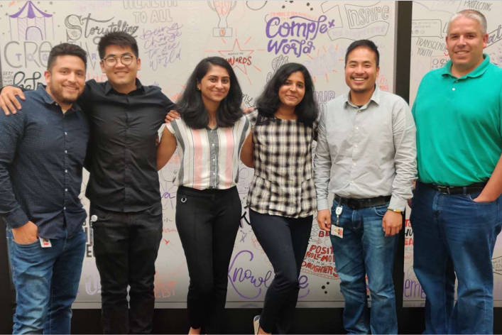 Group of ADP associates posing for a picture in front of a wall covered with inspiring words.