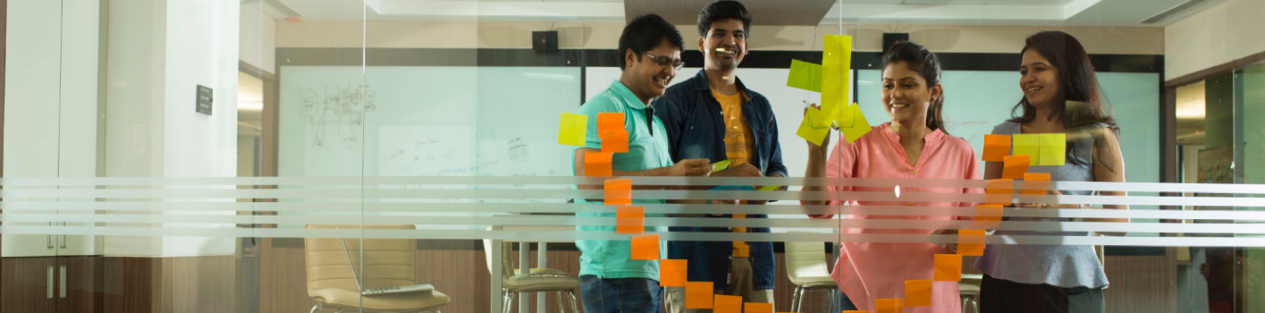 two men and women create a smiley face out of Post-it Notes on a glass wall