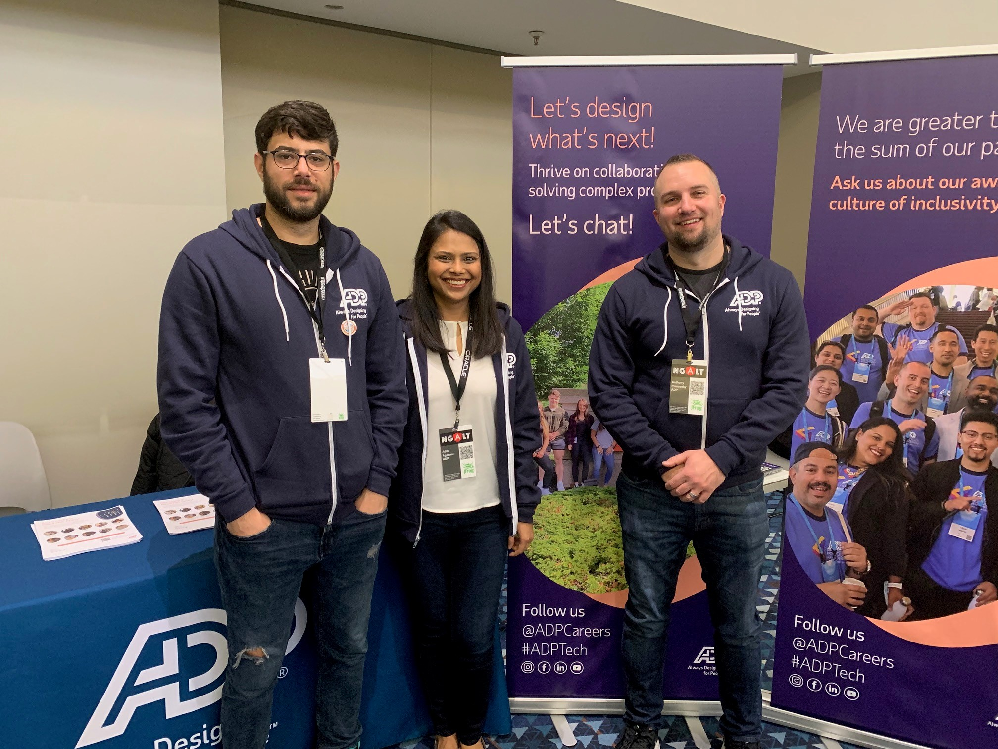 3 ADP employees in front of their event display booth