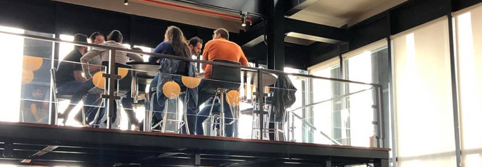 Two groups of employees seated around high tables