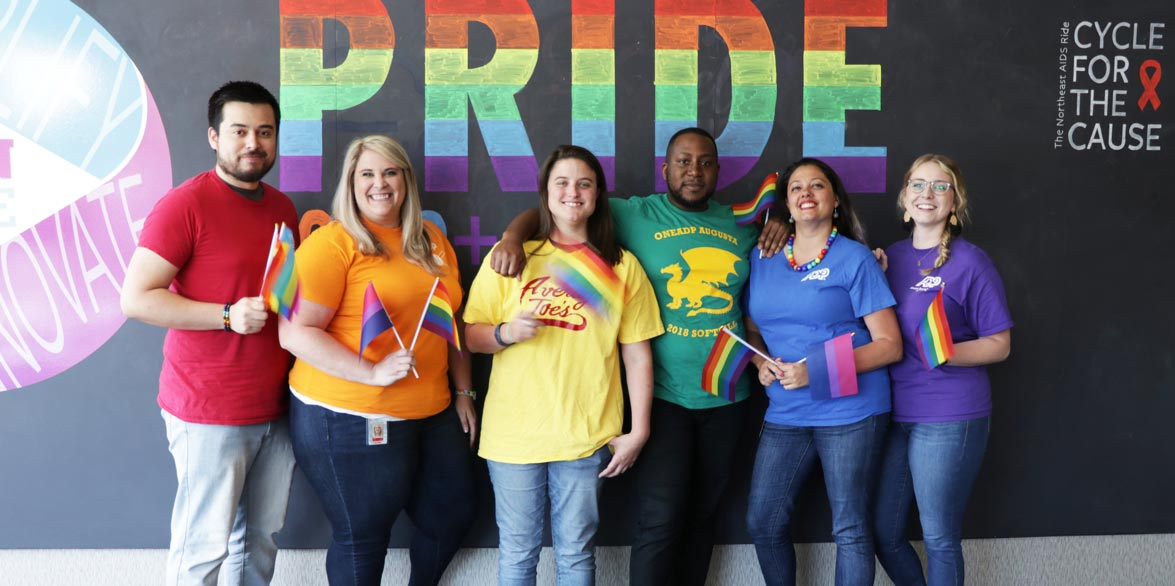 Group of people dressed in rainbow colors in front of a Pride sign