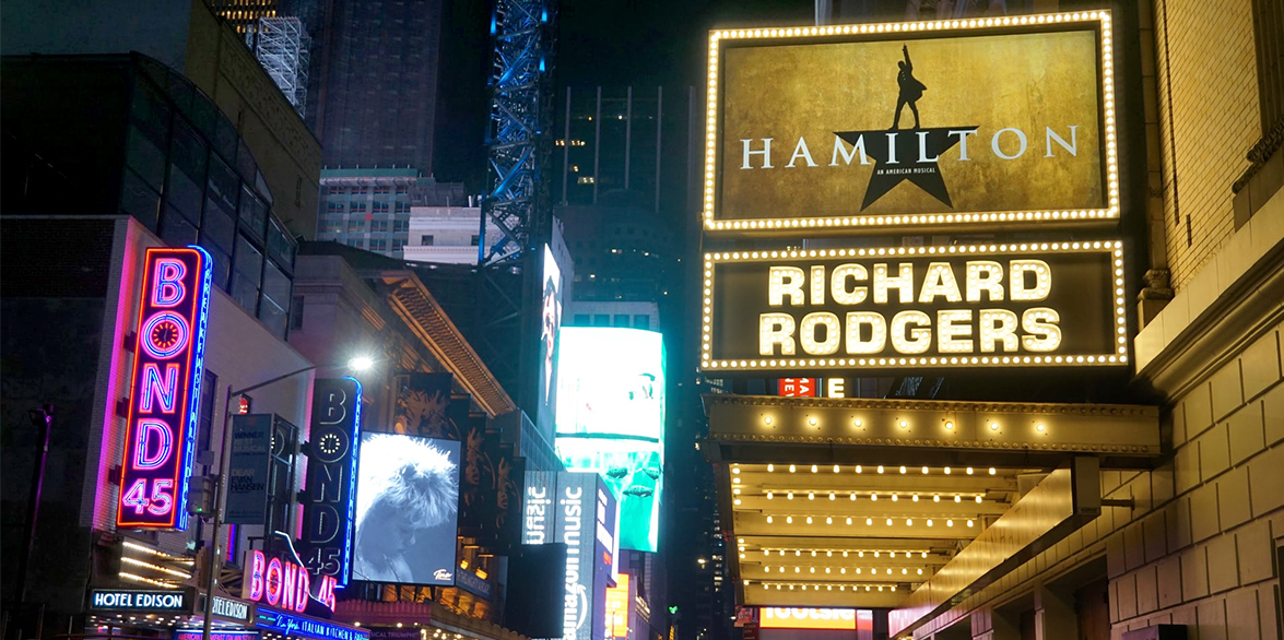 In New York City's Broadway District, a brightly lit, Richard Rogers Theatre marquee displays