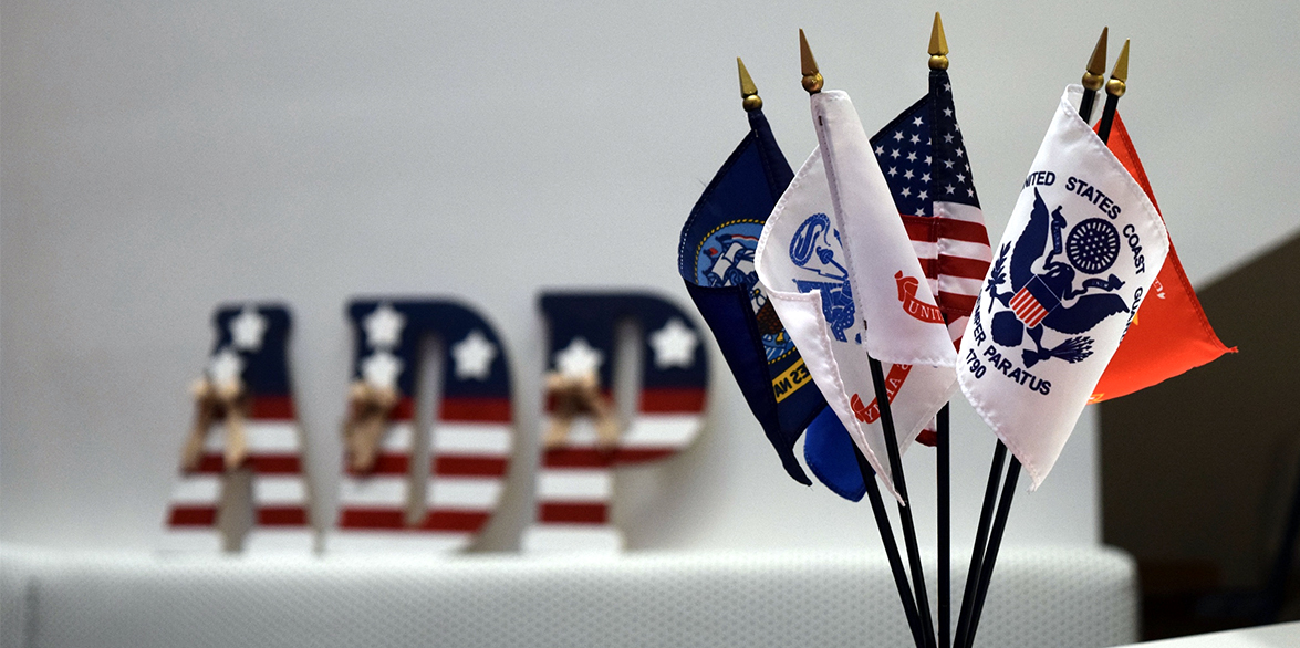 Miniature US and Military flags sit on the corner of a table with a stars and stripes ADP plaque in the background.