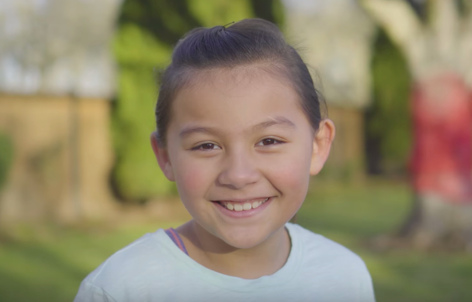 Smiling girl screen capture for video highlighting Chili's commitment to charitable giving