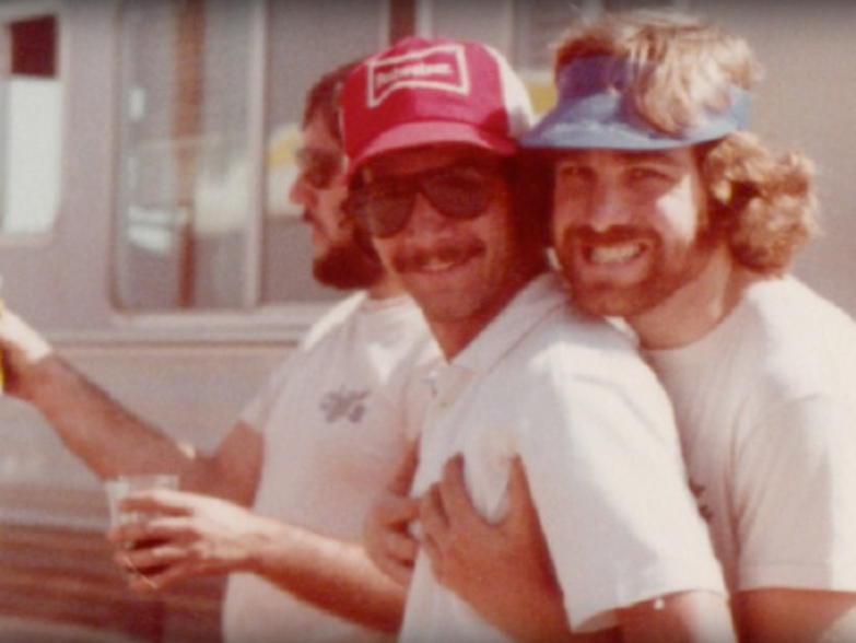 Chili's founder Larry Lavine and others smiling in an image from the history of Chili's video