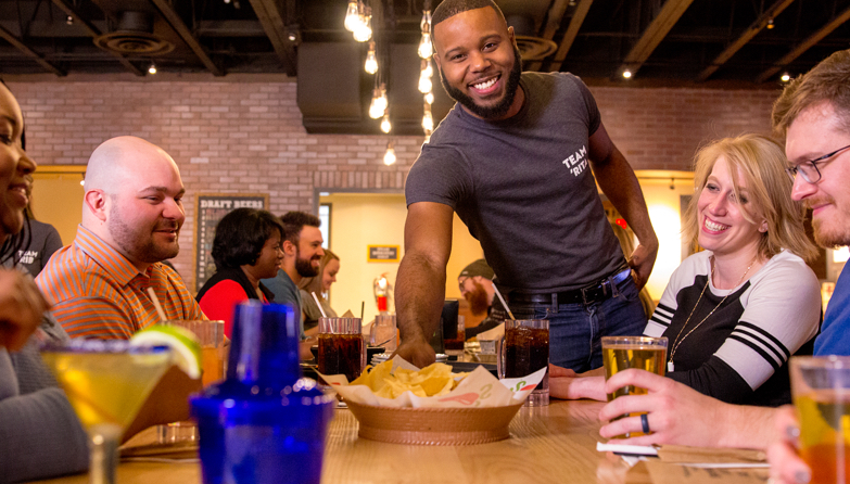 Chili's Server serving nachos to table of happy Guests
