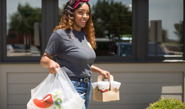 Chili's Team Member carrying fresh Chili's food to car in Chili's To-Go area