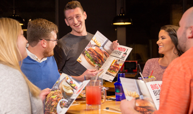 Smiling Chili's Server interacting with smiling Guests at their table