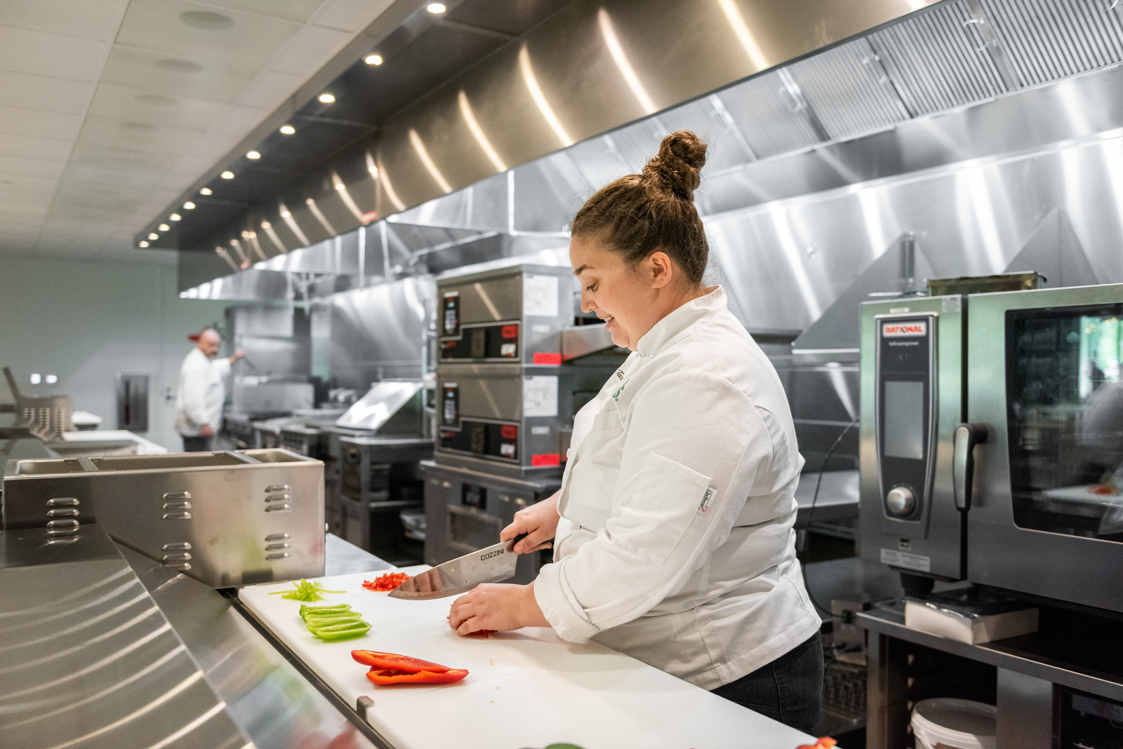 Female Chili's chef cutting vegetables in gleaming, clean stainless-steel Chili's kitchen
