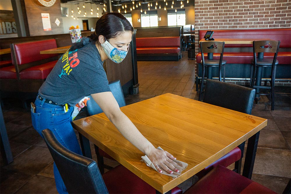 Chili's Team Member with protective mask cleaning and disinfecting restaurant table