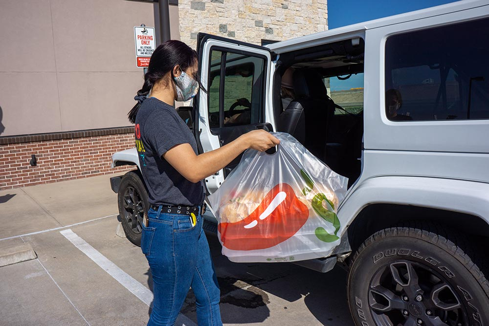 Chili's Team Member with protective mask approaching back of Guest's car to load delicious take-out food
