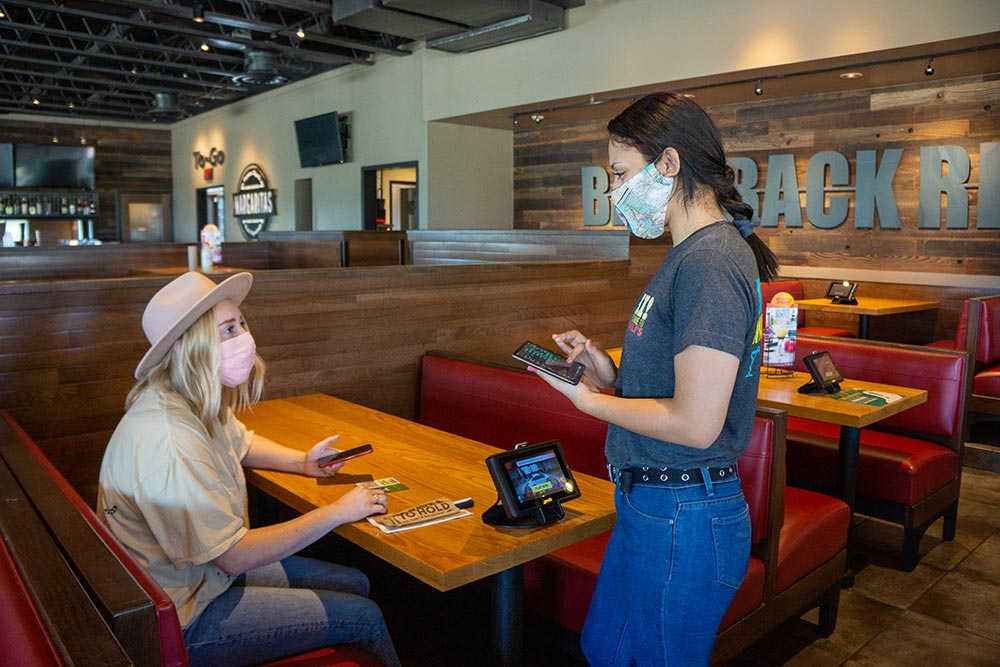 Chili's Team Member with protective mask taking Guest's order on electronic tablet at restaurant booth