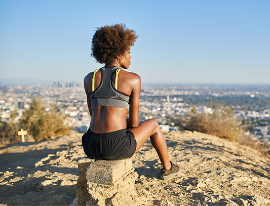 Woman in exercise clothes sitting on a rock overlooking a cityscape