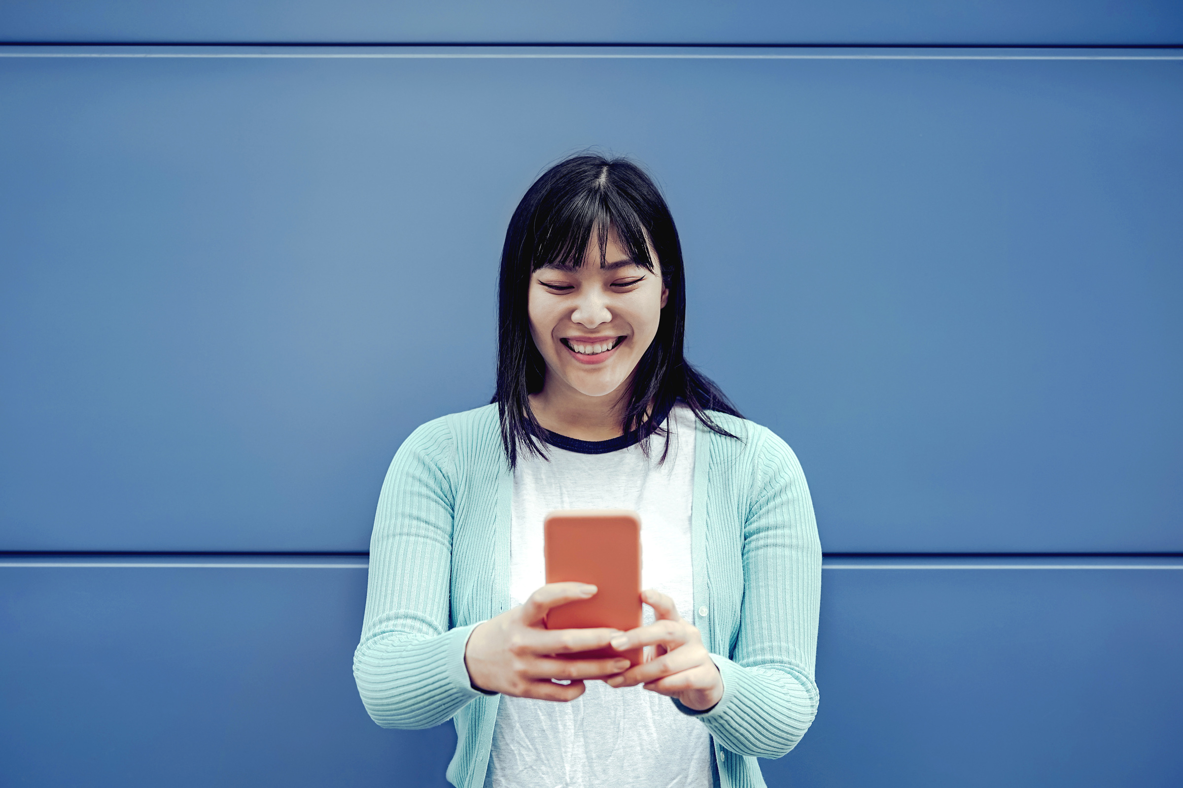 Woman smiling while using smartphone