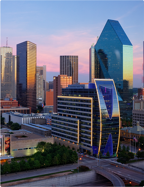 Several buildings in the Dallas city skyline reflecting the setting sun