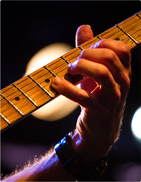 A hand strumming along the neck of a guitar