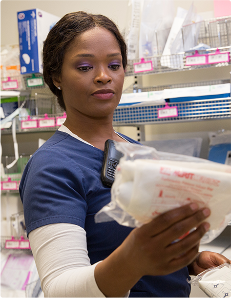 A nurse holding and reading the label on some medical supplies