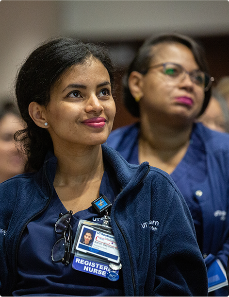 Smiling nurse looking forward in a crowded room surrounded by other seated medical professionals