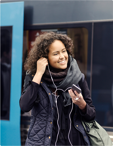 A smiling woman putting her headphones in her ears as she walks away from a commuter train