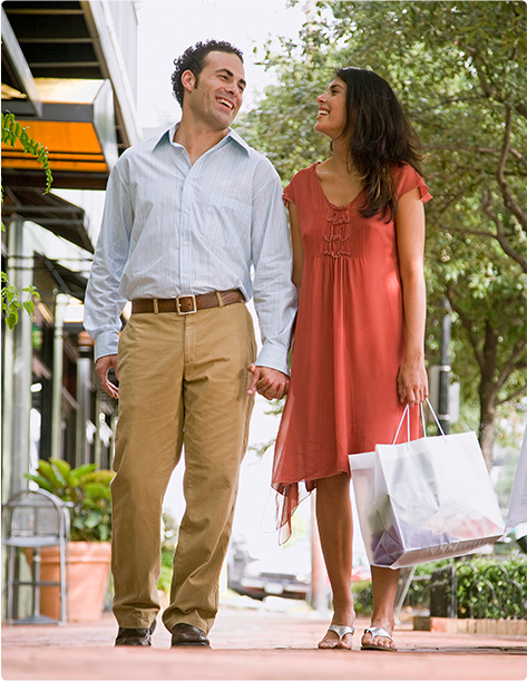 A man and woman walking hand in hand as they shop along a modern storefront