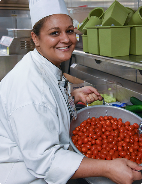 A smiling chef pulling a colander of bright red tomatoes from the sink