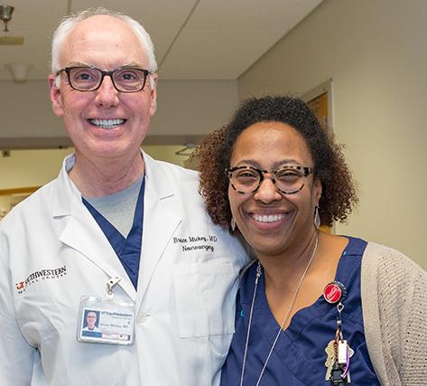 A doctor and nurse standing shoulder to shoulder and smiling