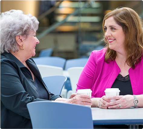 Two women sitting at a table in a hospital cafeteria drinking coffee and talking