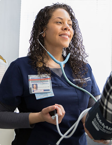 Smiling nurse holding a stethoscope and taking a patient's blood pressure
