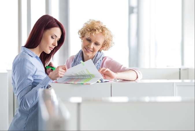 Two women reviewing paperwork surrounded by cubicles