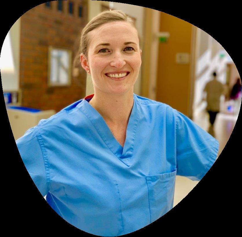 A smiling nurse in a hospital hallway.
