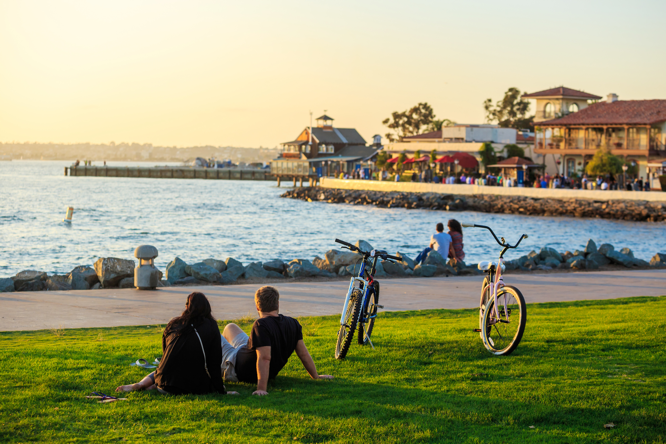Cyclists take a break near the waterfront to enjoy the setting sun.