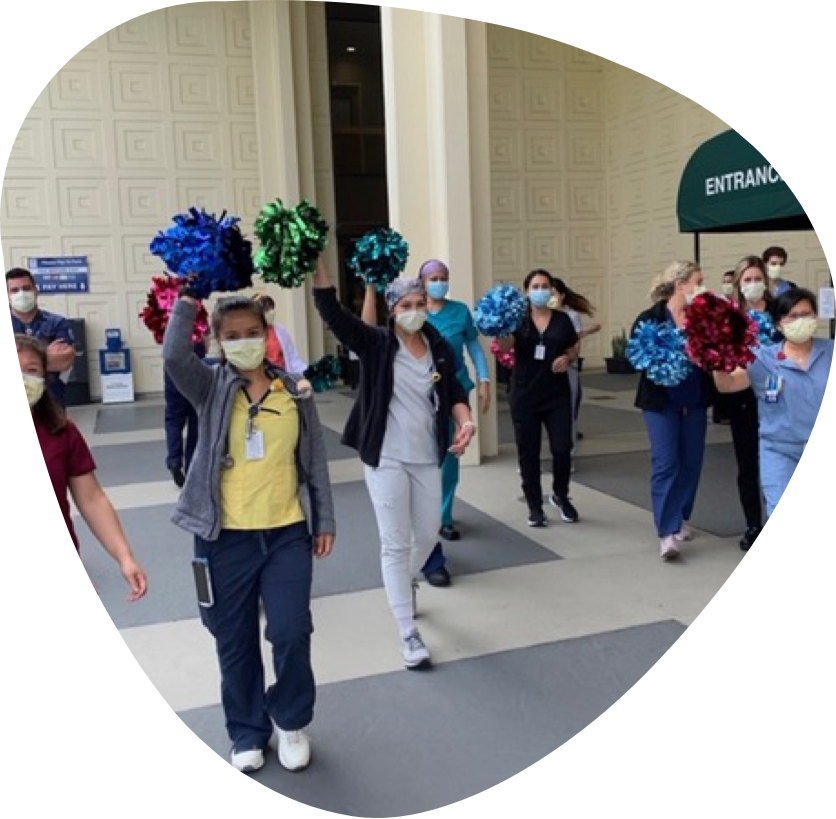 A group of nurses wearing masks parading and cheering in front of the hospital.