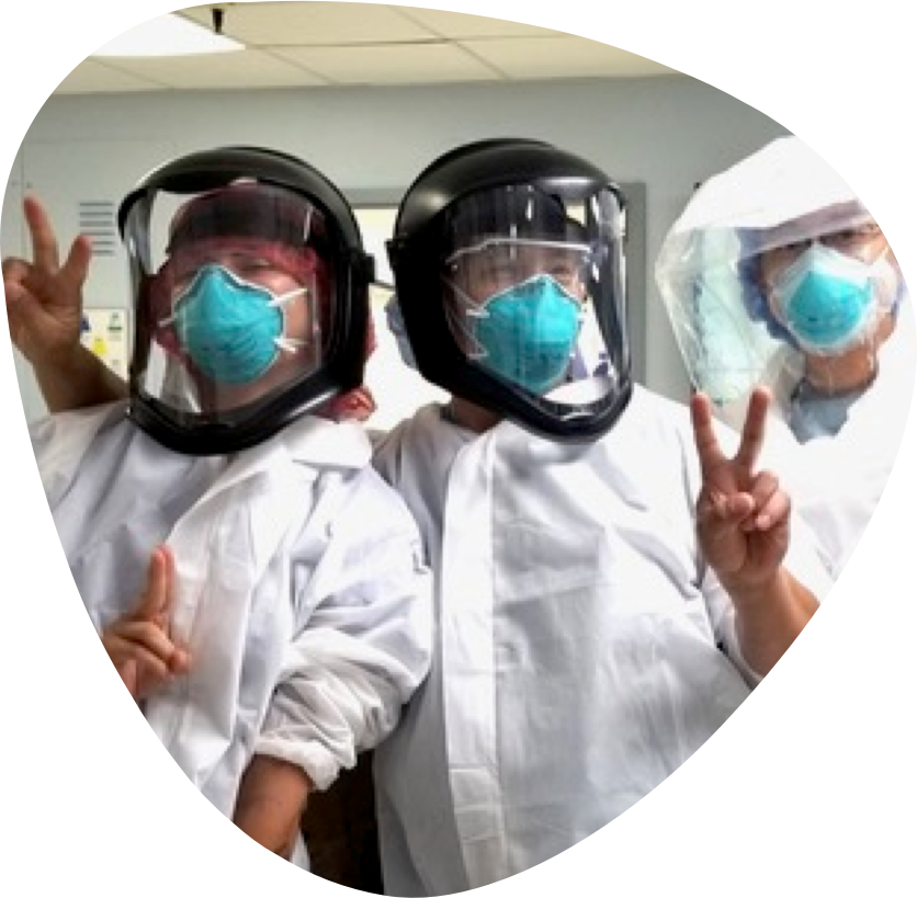 Three medical professionals dressed in PPE striking various playful poses.