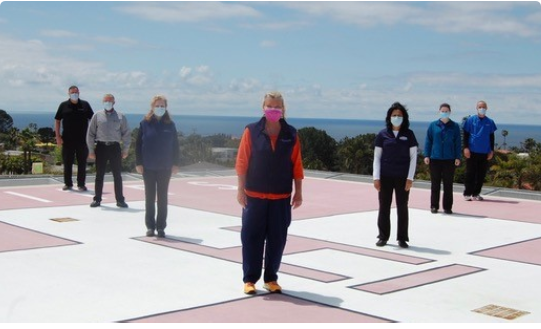 """Medical professionals in masks standing six feet apart on the hospital helipad. """