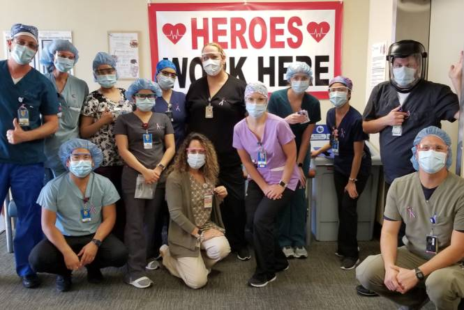 A group of medical professionals in PPE standing in front of a 'Heroes Work Here' sign.