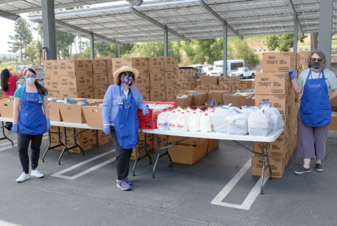 Three volunteers wearing masks at a food drive.