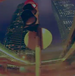 Close-up photo looking up at traffic light, tall buildings in the background