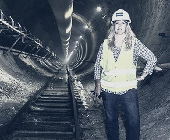 Female engineer wearing hard hat inside underground tunnel