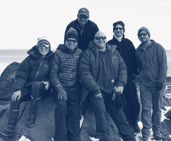Parsons employees in parkas sitting on large rock on snowy beach