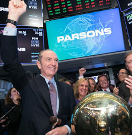 Parsons executives on floor of stock exchange in front of large monitor displaying Parsons' name