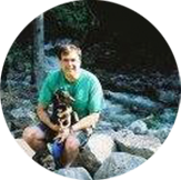 Parsons employee Chris Miles sitting by river holding his dog