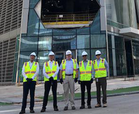 Parsons engineers with hard hats posing in front of glass entrance to large building